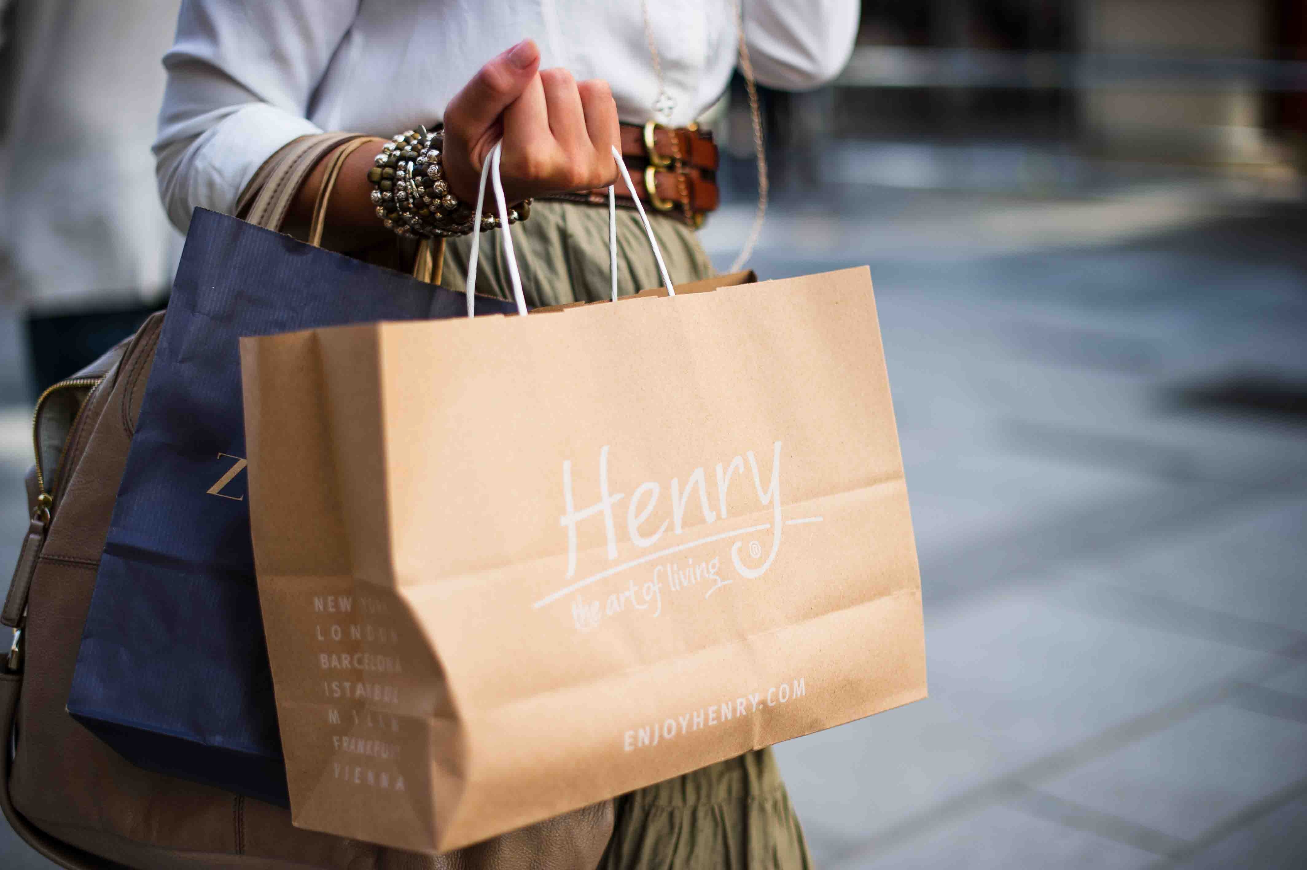 why people buy represented by hand holding shopping bags
